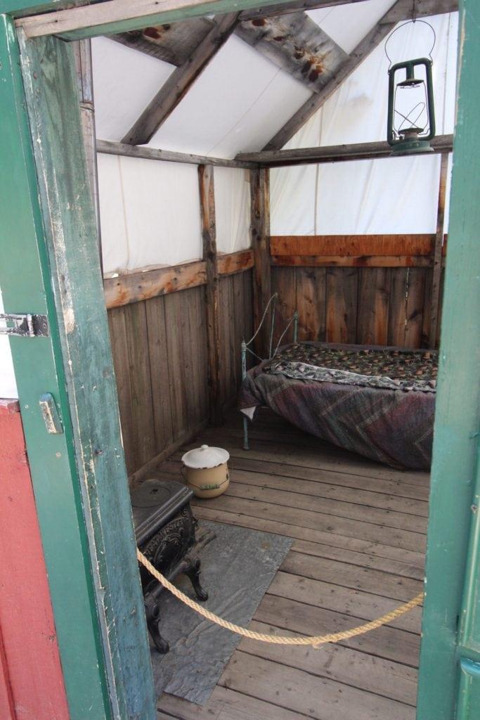 cot in log cabin room